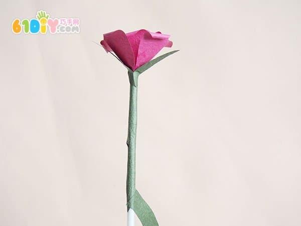 ,剪下来得到9个爱心。一朵花只需要6片爱心,剩下的可以做另外的花。  取一片爱心用笔芯卷起来   把第一片花瓣用双面胶如图粘贴好  第二片爱心对折  用笔芯把边沿卷成花瓣的卷边  粘贴好第二片花瓣  其它花瓣都和第二片花瓣一样操作  粘贴好花瓣的玫瑰花  用绿色纸剪成如图的形状做花萼  卷到花瓣的下面  用绿色之剪1.
